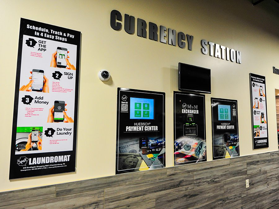 Spot laundromat's currency station with Huebsch Pay system in English and Spanish.